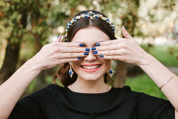 Moda, uroda, czułość, manicure. młoda szczęśliwa kobieta z jasnym uśmiechem manicure szerokim, białym uśmiechem, prostymi białymi zębami. dziewczyna zakrywa twarz rękami. opaska do włosów, kolczyki, niebieski lakier do paznokci.