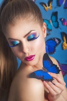 Moda uroda dziewczyna z motylem na dłoni.
