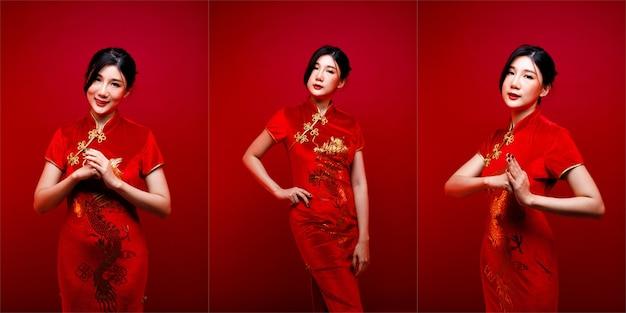 Moda uroda kobieta ma długie, proste, czarne włosy, patrzy w kamerę i wyraża uczucie świętowania. portret azjatyckiej dziewczyny nosić czerwoną chińską sukienkę na czerwonym tle, kopia przestrzeń