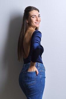 Moda uroda portret młodej kobiety w niebieskie ciało, dżinsy, białe tło. udana piękna, pewna siebie uśmiechnięta kobieta ze zdrowymi białymi zębami, prostymi zdrowymi włosami