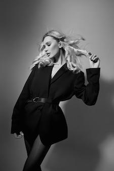 Moda uroda sexy kobieta w kurtkę i rajstopy, blondynka z długimi nogami. idealna figura modelki, portret kobiety na szarym tle