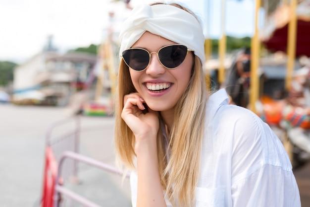 Moda uśmiechnięta słodka młoda kobieta z rblond włosami, śmiejąca się z kamery w białej koszuli i białych akcesoriach do włosów i czarnych okularach przeciwsłonecznych na ulicy przez atrakcje