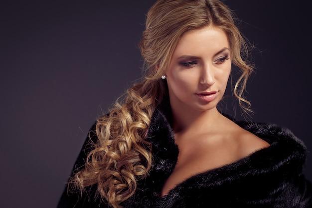Moda uwodzicielska blond dama w eleganckim futrze i czarnej bieliźnie