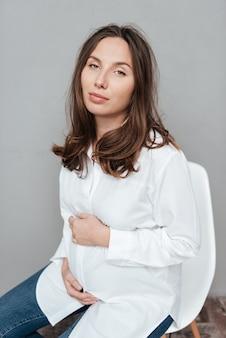 Moda w ciąży kobieta w studio siedzi na krześle na białym tle szarym tle