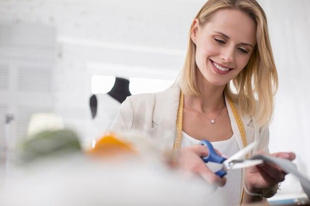 Moda wewnętrzna. niski kąt energicznej krawcowej kobiety pracującej z materiałem i wykonującej krój