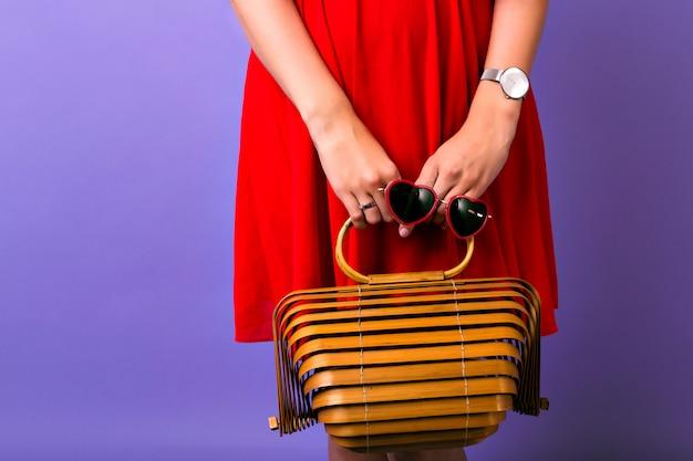 Moda z bliska zdjęcie lub kobieta ubrana w elegancką jasnoczerwoną sukienkę, trzymając słomkową drewnianą modną torbę i okulary przeciwsłoneczne w kształcie serca, prosty zegarek, fioletowe tło.
