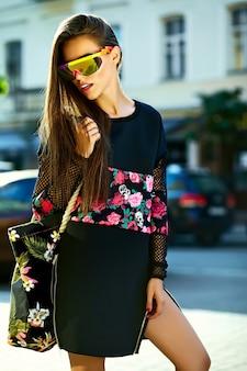 Moda zabawny seksowny stylowy seksowny uśmiechający się piękna młoda kobieta model w czarne hipster letnie ubrania na ulicy po zakupach