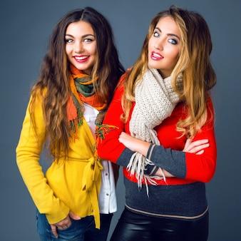 Moda zimowy portret blondynki i brunetki pięknych najlepszych przyjaciółek, przytula i zabawy. nosi jasne, stylowe kaszmirowe swetry i szaliki. miej modny makijaż i długie, niesamowite włosy.