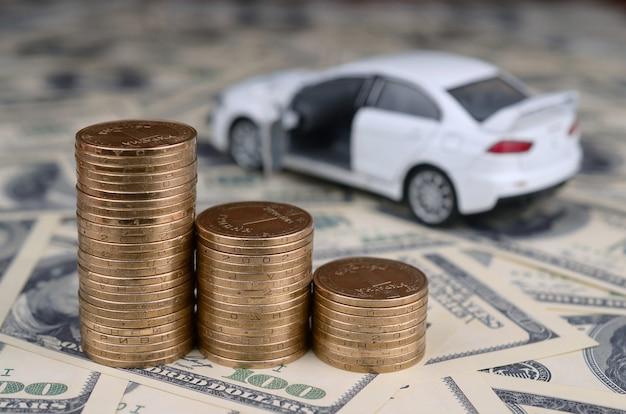 Model autka na stosach złotych monet leży na wielu banknotach dolarowych