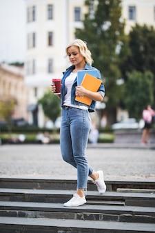 Model blondynka idzie na zajęcia robocze przez citycentre, trzymając w rękach komputer z notebookami do kawy rano