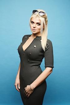 Model blondynka z jasny makijaż w obcisłą sukienkę pozowanie na niebieską ścianą