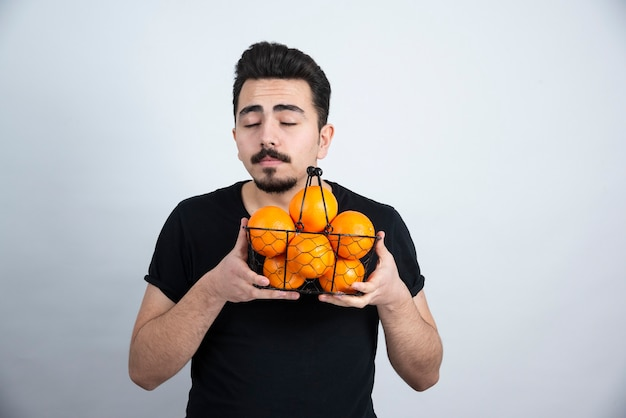 Model brunetka mężczyzna stojący i trzymając metalowy kosz z pomarańczowymi owocami.