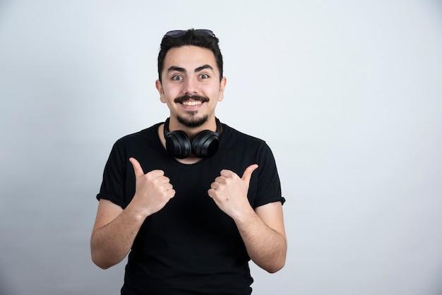 Model brunetka mężczyzna stojący w słuchawkach i pokazujący kciuki do góry na białej ścianie.
