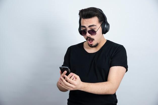 Model brunetka mężczyzna w okularach przeciwsłonecznych i słuchawkach, trzymając telefon komórkowy.
