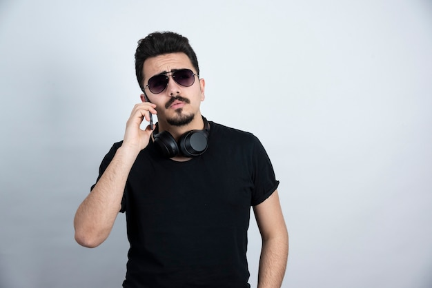 Model brunetka mężczyzna w okulary i słuchawki rozmawia przez telefon komórkowy.