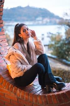 Model brunetka siedzi w zimie z miastem w tyle