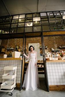 Model brunetka w krótkich włosach pozowanie w białej sukni ślubnej