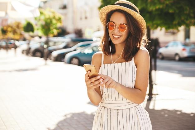Model brunetka w letnie ubrania pozowanie na ulicy przy użyciu telefonu komórkowego