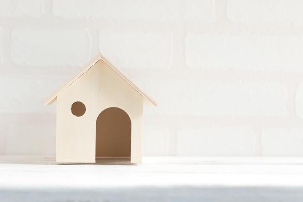 Model dom na białym drewnianym stołowym ceglanym tapetowym tle. koncepcja domu biznesu.
