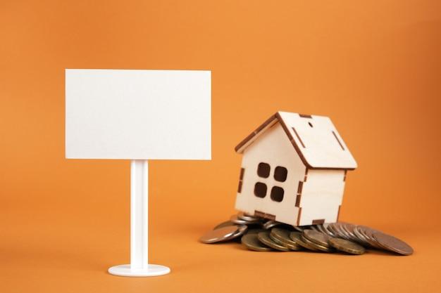 Model domu, biały pusty znak i stos monet na brązowym tle