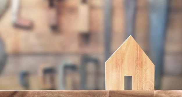 Model domu drewnianego na drewnianej powierzchni. dom, koncepcja nieruchomości mieszkaniowej