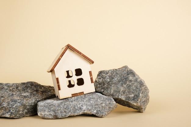 Model domu i kamienie na beżowym tle kopia przestrzeń