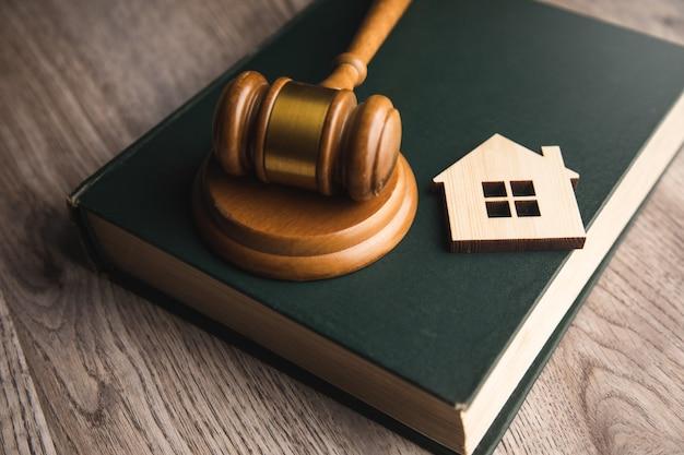 Model domu, młotek i książki prawnicze