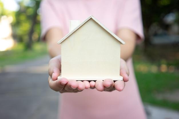 Model domu model jest umieszczony na rękach azjatyckich business girl.