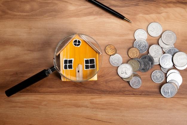 Model domu, monety i szkło powiększające na drewnianym stole