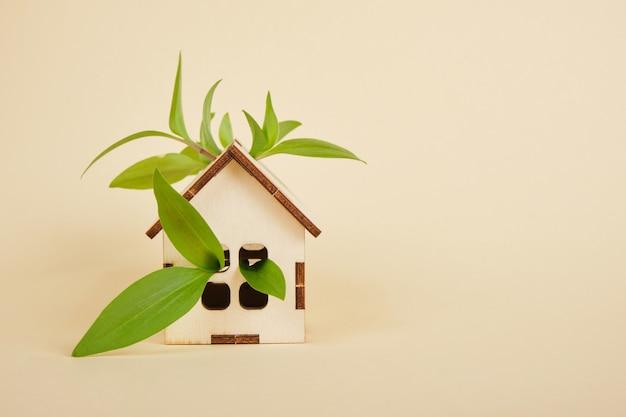 Model domu na beżowym tle, koncepcja domu ekologicznego, zielone liście i miejsce na kopię domu zabawki