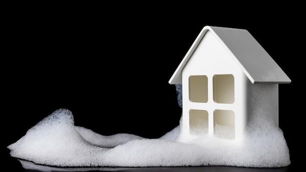 Model domu na czarnym stole z wieloma bańkami i czarnym tłem, rynek nieruchomości, nieruchomości handlowe, kredyt hipoteczny, bańka ekonomiczna, koncepcje bańki cen aktywów