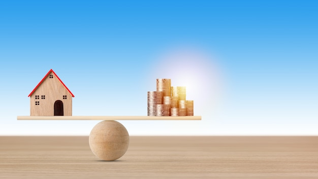 Model domu na huśtawce równoważenia z układaniem monet pieniędzy na niebieskim tle.