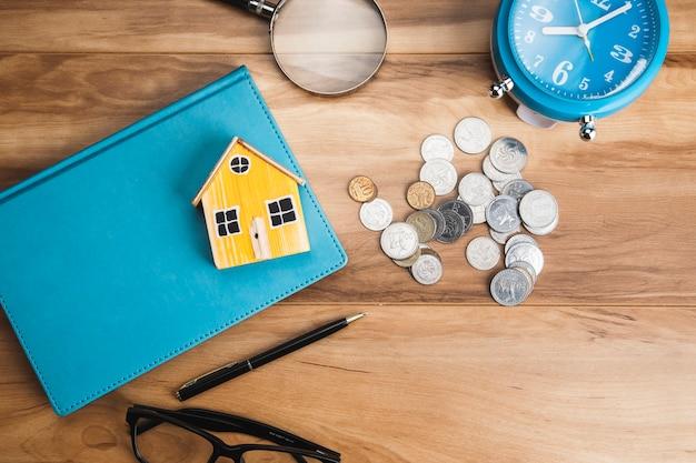 Model domu na książce z monetami na stole