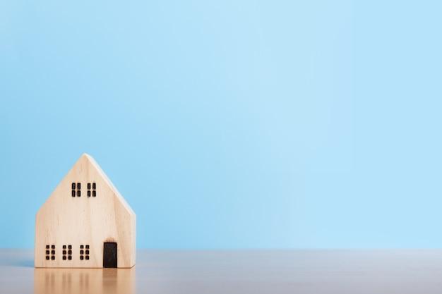 Model domu na niebieskim tle. dom rodzinny, ubezpieczenia i nieruchomości inwestycyjne koncepcja nieruchomości. miejsce na kopię.