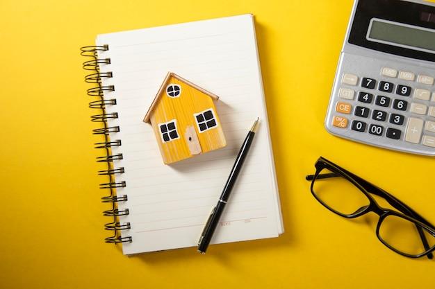 Model domu na notebooku i kalkulator na stole