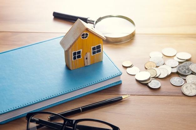 Model domu na notebooku z monetami na stole