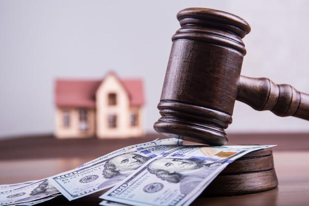 Model domu na pieniądze dolarów z młotem sędziego jako koncepcja inwestycji hipotecznych