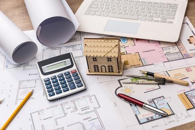 Model domu na rysunku architekta z laptopem i kalkulatorem