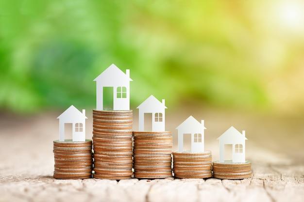 Model domu na stosie monet do oszczędzania na zakup domu