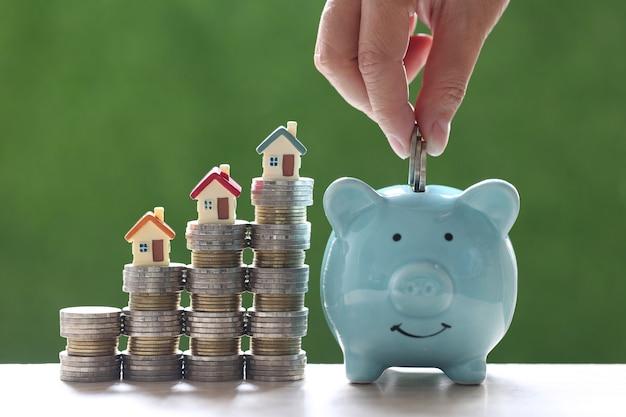 Model domu na stosie monet pieniędzy na naturalnym zielonym tle