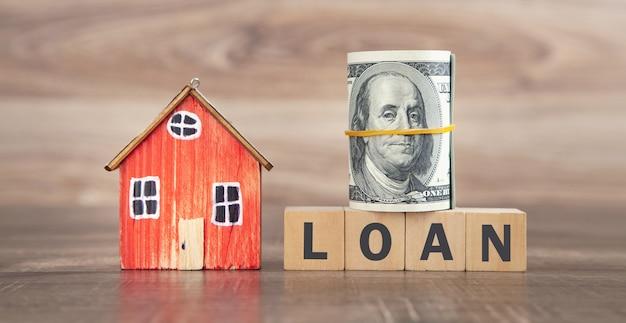 Model domu, pieniądze i pożyczka słowo na drewnianych kostkach.