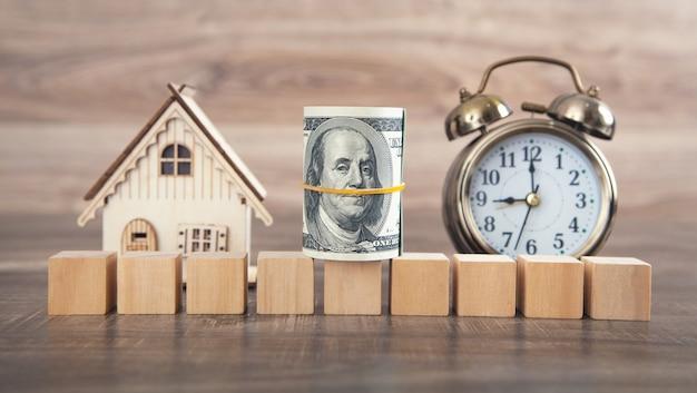 Model domu, pieniądze i puste drewniane kostki.
