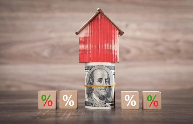 Model domu, pieniądze, z symbolem procentu na kostkach.