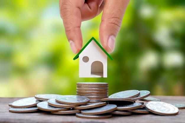 Model domu trzymającego się za ręce na stosie monet z rozmytym zielonym naturalnym tłem pożyczka domowa