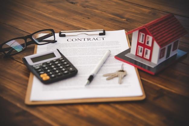 Model domu umieszczony na kontrakcie umieszczony na drewnianym stole, hipoteka i inwestycja w nieruchomości, ubezpieczenie domu, koncepcja bezpieczeństwa.