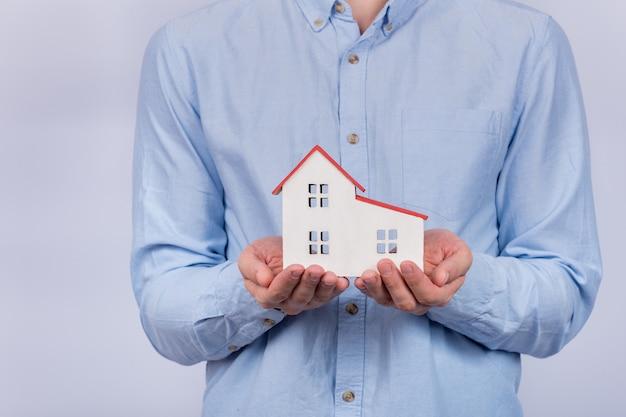 Model domu w męskich rękach. kupno domu, koncepcja kredytu hipotecznego