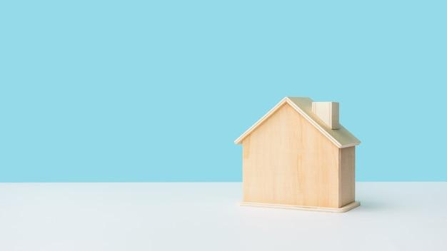 Model domu wykonany z drewna z niebem na pastelowym tle