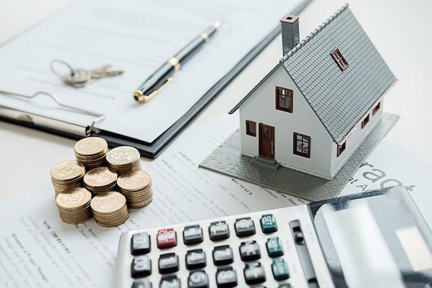 Model domu z agentem nieruchomości i klientem dyskusji na temat umowy na zakup domu, ubezpieczenia lub pożyczki w tle nieruchomości.