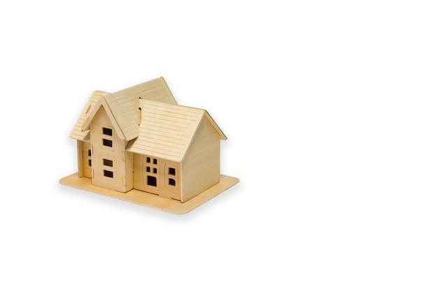 Model domu z drewna na białym tle, koncepcji finansowej i biznesowej.