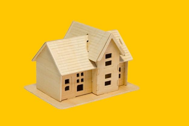 Model domu z drewna na białym tle na żółtym tle, koncepcji finansowej i biznesowej.